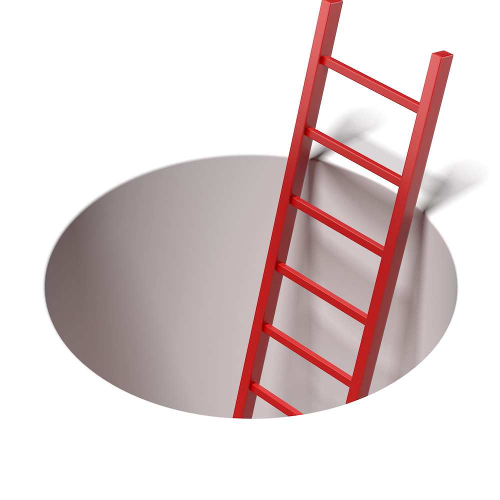 Ladder standing inside hole isolated on a white background